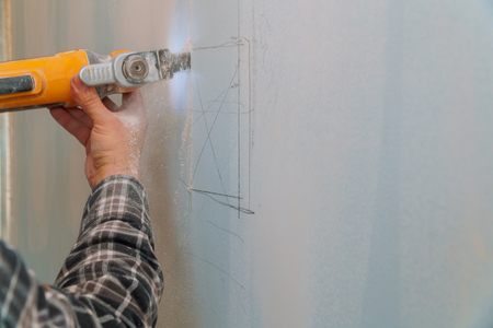 Construction worker cutting gypsum drywall by using electric cutter angle grinder Reklamní fotografie