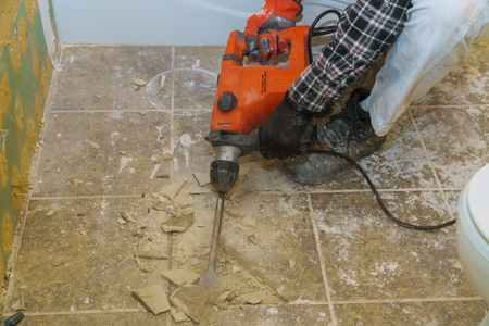 Worker demolish old tiles remove in a bathroom with hammer