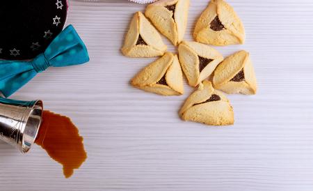 Jewish holiday Purim with carnival mask and homemade hamantaschen cookies, kippah red kosher wine flat lay Stock Photo