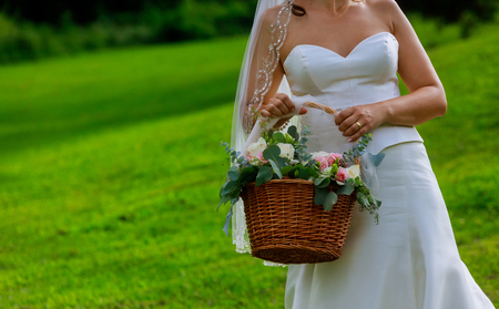 Close up a flower girl a white dress with flowers holding a basket