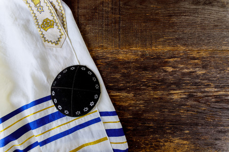 Jewish prayer items kippa and tallit on a wooden table Stock Photo