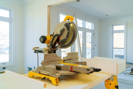 Cutting wooden trim board on with circular saw works on remodeling home Foto de archivo - 118927074