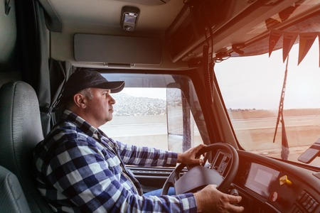 Driver in cabin of big modern truck vehicle on highway Stock Photo