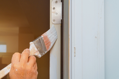 Professional painter cutting in with brush man is painting door with brush Standard-Bild - 119984463