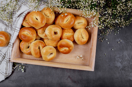 Delicious homemade golden buns in tray, vintage wooden rustic table background, selective focus