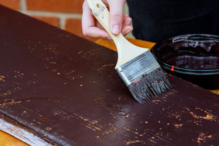 Contractor painting a wooden baseboard for renovation in a new house Standard-Bild - 119984796