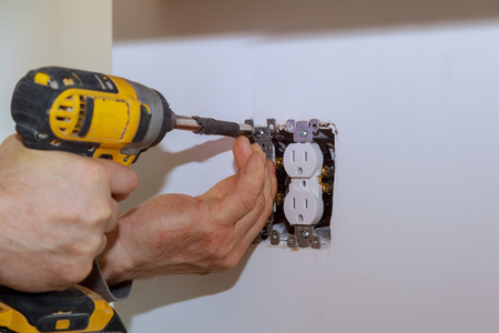Electrician installs lighting switch in the wall using screwdriver