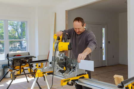 Carpenter using a circular saw to cut wood baseboard interior construction of new housing Banque d'images - 123108606