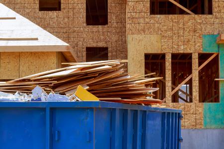 Vista residenziale di nuove case in costruzione e grande contenitore di rifiuti da costruzione