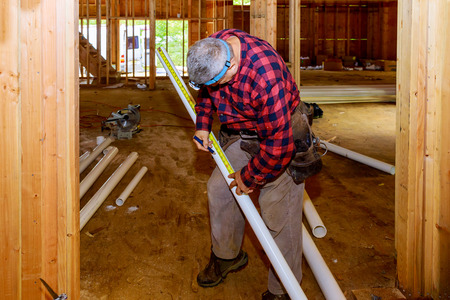 Worker using a cutting plastic PVC pipe special scissors in construction