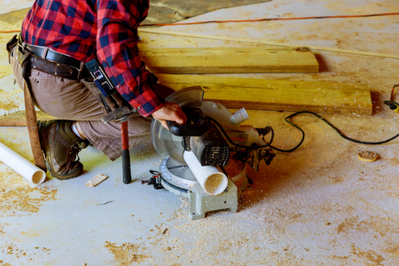 Worker using electric saw cutting pvc pipe in construction a new commercial construction