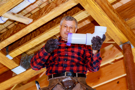 Plumber worker installing sewage pipes in supply system in a private house. Stock Photo