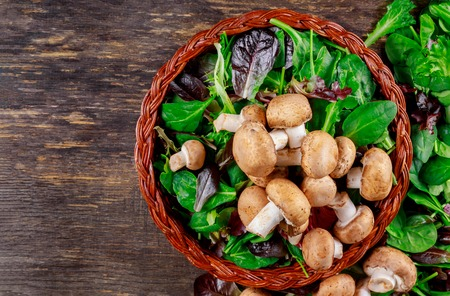 Basket salad with mushrooms, on rusty old wood background