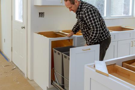 Handyman in installed drawers garbage bin in the kitchen
