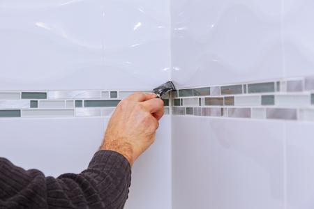 Renovación de mejoras para el hogar aplicando sellador de silicona con el trabajador de la construcción llena la costura de las baldosas de cerámica en la pared del baño