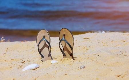 Trendy slippers on white sandy ocean beach.