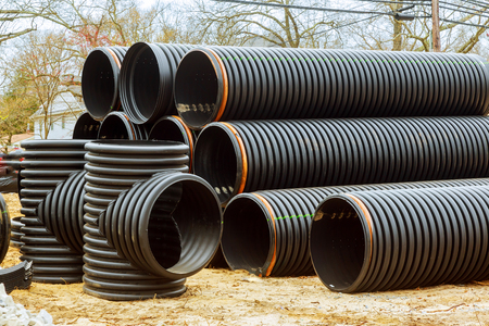 Under construction of housing of stacked PVC pipes on building Stock Photo