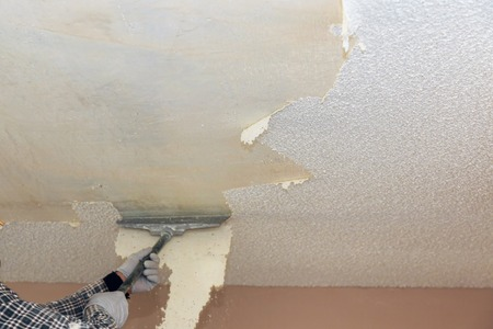Take off in the popcorn ceiling home wall texture removal ceiling drywall demolition Фото со стока