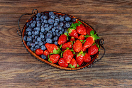 Mix of fresh healthy vith blackberries and strawberriesin a basket on rustic wooden background