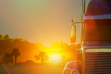 Truck dashboard on the countryside road in motion against with sunset