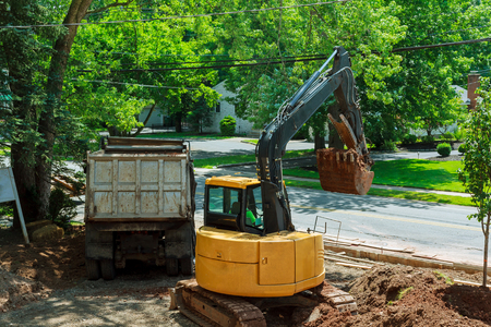 Yellow heavy duty digger working in excavation pit on background of residential complex