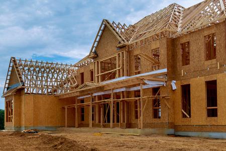 La nuova costruzione di una casa di costruzione di travi ha incorniciato l'inquadratura da terra contro un cielo blu Archivio Fotografico
