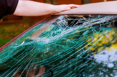 Glass broken cracks splinters in front of car front window. Stock Photo