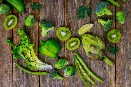 Assortment of fruits fresh green vegetables on a wood background. Stok Fotoğraf
