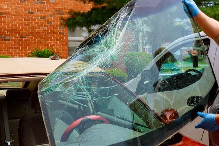 Les travailleurs spéciaux de la voiture pare-brise cassé prennent le pare-brise d'une voiture en service automobile de l'intérieur à la suite d'un accident de voiture. Banque d'images