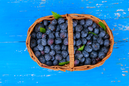 Healthy fresh organic blueberries in basket, selective focus a wooden table.