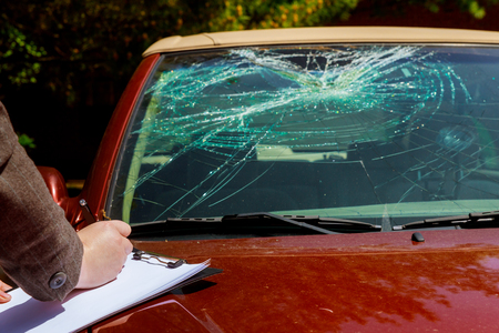 Insurance agent estimates the cost of damaged windshield after car accident, Archivio Fotografico