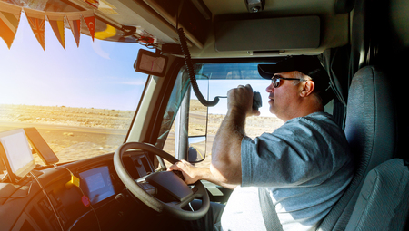 Truck drivers big truck right-hand traffic hands holding radio and steering wheel truck dashboard with driver Banco de Imagens