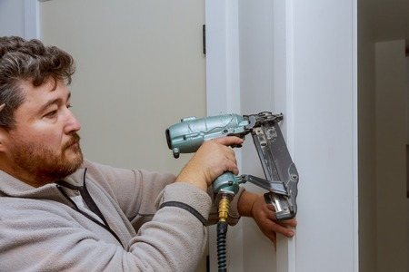 Carpenter using nail gun to moldings on door, framing trim, with the power tools