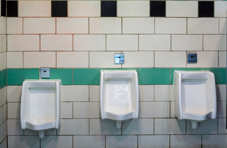 Men in toilet room white ceramic urinals in an building for men only, white urinals in men's bathroom Archivio Fotografico