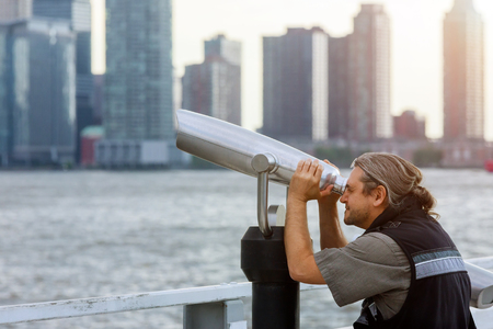Man tourist looking through binoculars. on top of New York Manhattan the Freedom Tower enjoying beautiful city travel and buildings landscape 写真素材