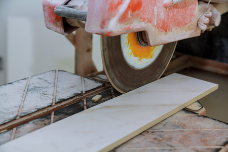 Circular saw cutting ceramic tile electro saw on the construction tile floor