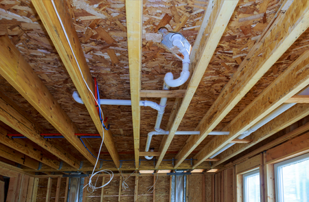 Waste PVC pipe drainage system inside building, piping on the ceiling of home Stockfoto