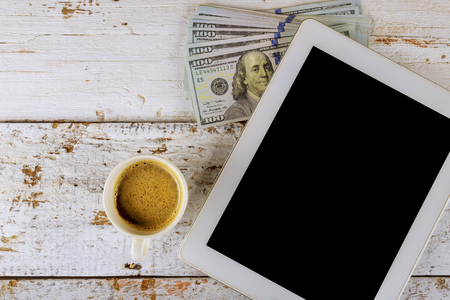 Business office tablet US dollars banknotes and coffee cup on wooden table Stockfoto