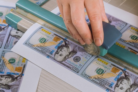 Cutting fake US dollars cutter banknotes, fake money currency counterfeiting