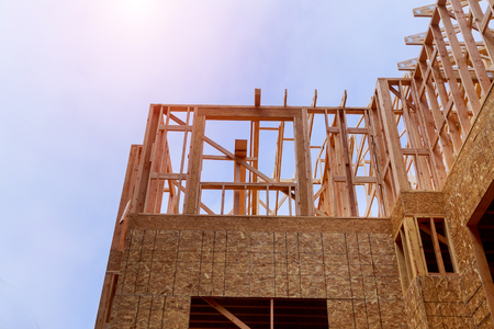 New construction beams under a clear blue sky with sunlight