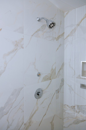 Detail of corner shower cabin with wall mount shower attachment