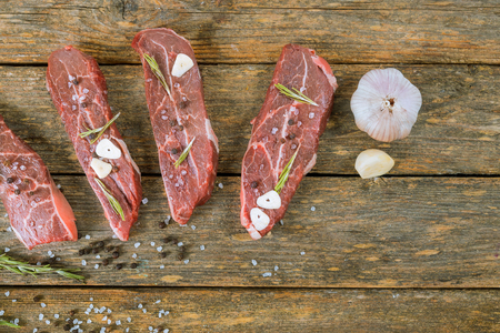Raw beef steak on a wooden table with rosemary and garlic