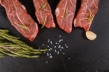 Raw beef steaks with spices with rosemary and garlic. Flat lay.