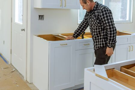 A carpenter is building a drawers garbage bin in the kitchen using a screwdriver.