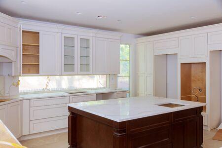 Interior design construction of kitchen with cabinet maker installing custom