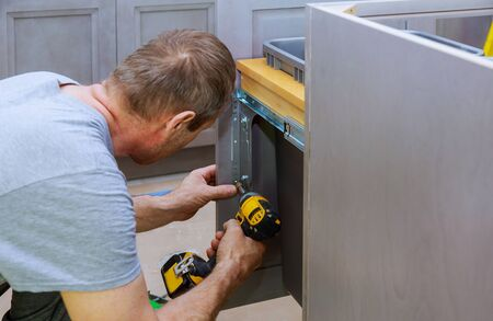 Installed drawers garbage bin with front for drawer inside screws using a screwdriver.