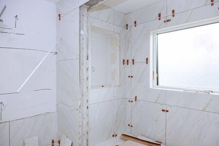 Travaillez la pose du carrelage avant d'appliquer le carrelage sur le carrelage de la salle de bain.