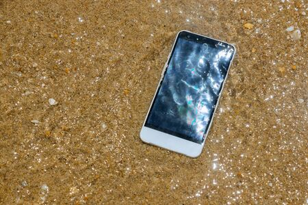 Broken crashed smartphone is lying in the water in the sandy beach