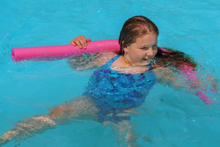 Cute smiling little girl in swimming pool in sunny day summer vacation