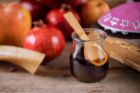 Apple and honey, traditional food of jewish New Year Rosh Hashana torah book, kippah a yamolka talit